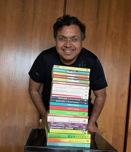 Devdutt Pattanaik, mythologist and author, with books written by him.