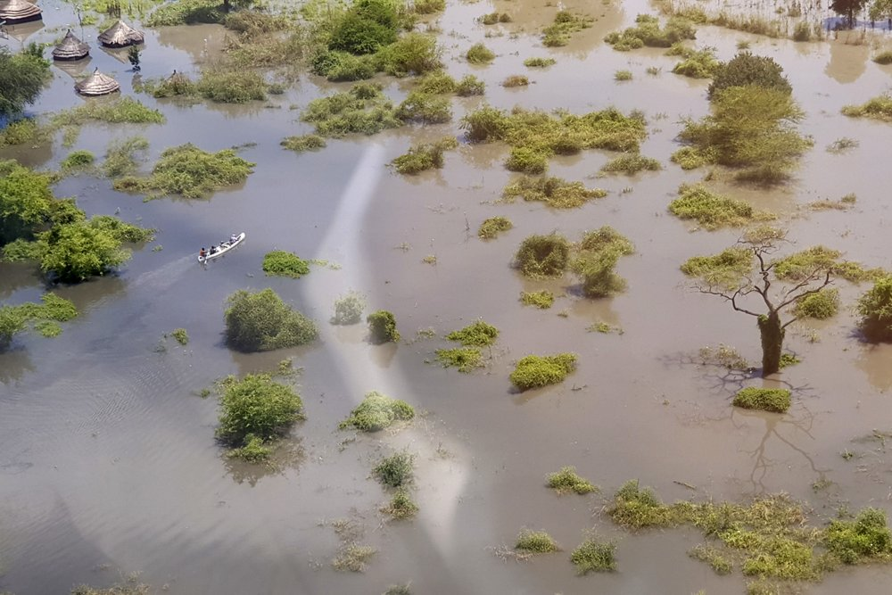 In this photo taken Saturday, Oct. 19, 2019 and released by Medecins Sans Frontieres, people in a canoe move through floodwaters between Gumuruk and Lekongole, seen from the air, in South Sudan. South Sudan's president on Tuesday, Oct. 29, 2019 declared a state of emergency in 27 counties because of the flooding and parts of the East African region are bracing for a tropical storm that could worsen an already dire humanitarian situation. (Medecins Sans Frontieres via AP)