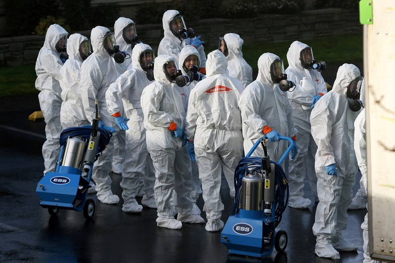 Members of a Servpro cleanup crew wearing hazardous material suits prepare to enter Life Care Center of Kirkland, the Seattle-area nursing home at the epicenter of one of the biggest coronavirus outbreaks in the United States. (Image, Reuters)