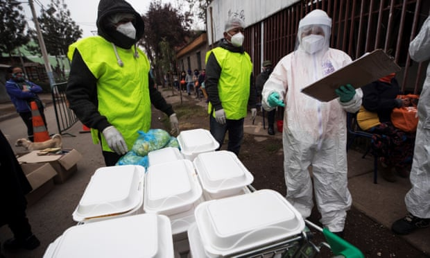 Workers prepare and deliver food for people affected by the coronavirus pandemic, in Santiago, Chile. (Image, Alberto Valdés/EPA)