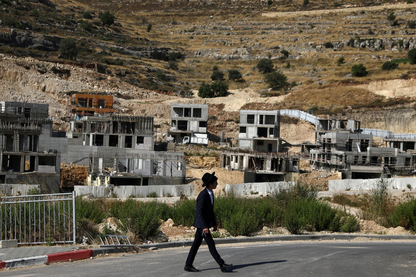 A Jewish settler walks past Israeli settlement construction sites in the Israeli-occupied West Bank near Jerusalem on June 30. (Ammar Awad/Reuters)