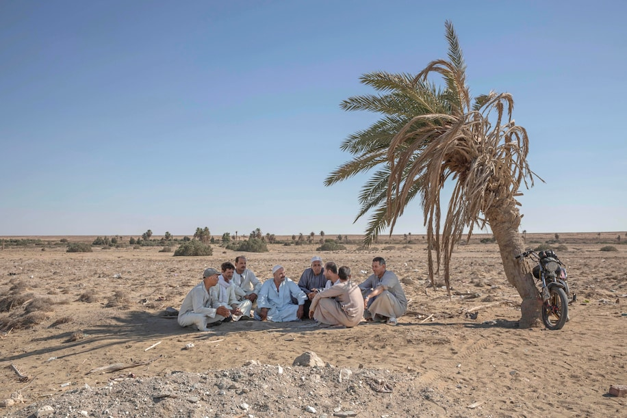 """55-year-old Egyptian farmer Makhluf Abu Kassem, center, sits with farmers under shade of a dried up palm tree surrounded by barren wasteland that was once fertile and green, in Second Village, Qouta town, Fayoum, Egypt, Wednesday, Aug. 5, 2020. Abu Kassem fears that a dam Ethiopia is building on the Blue Nile, the Nile's main tributary, could add to the severe water shortages already hitting his village if no deal is struck to ensure a continued flow of water. """"The dam means our death,"""" he said. (Nariman El-Mofty/Associated Press)"""