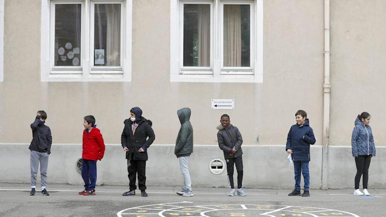 In this Thursday, May 14, 2020 file photo, schoolchildren wait in line to go back in their classroom at the Sainte Aurelie primary school of Strasbourg. (Image by Jean-Francois Badias)