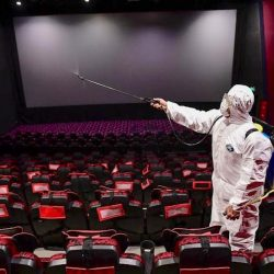 This photo taken on March 25, 2020 shows a staff member spraying disinfectant at a cinema as it prepares to reopen to the public after closing due to the COVID-19, in Shenyang in China's Liaoning province. (PHOTO/AFP)